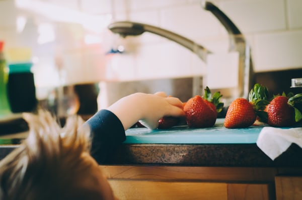 small child trying to reach strawberries on a kitchen bench