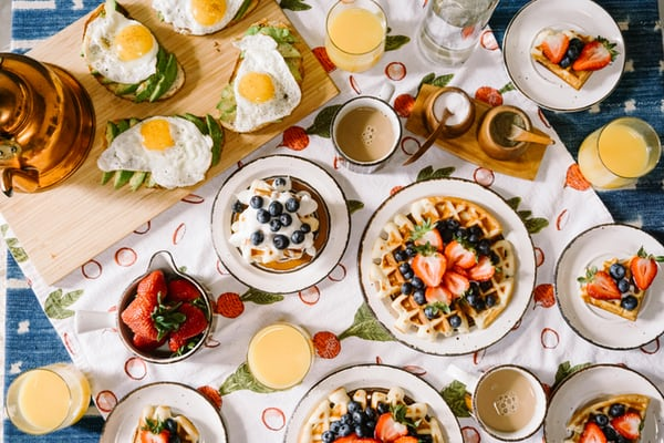 top view of a breakfast table with waffles, eggs and fruit