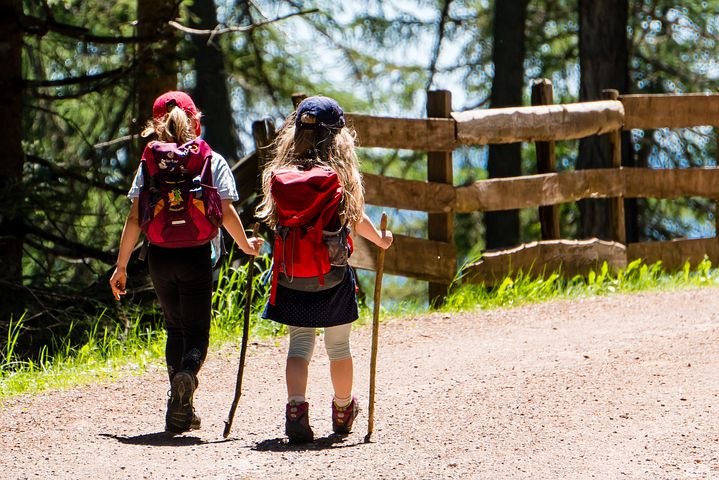 two children hiking with backpacks