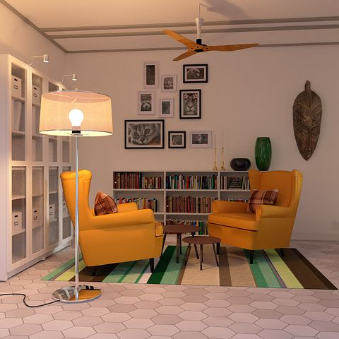 two sofa chairs in a corner with bookshelves
